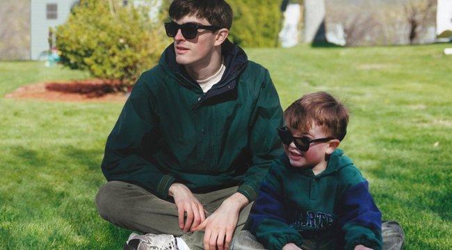 Ez a fiatal saját gyerekkori önmaga mellett áll a képeken